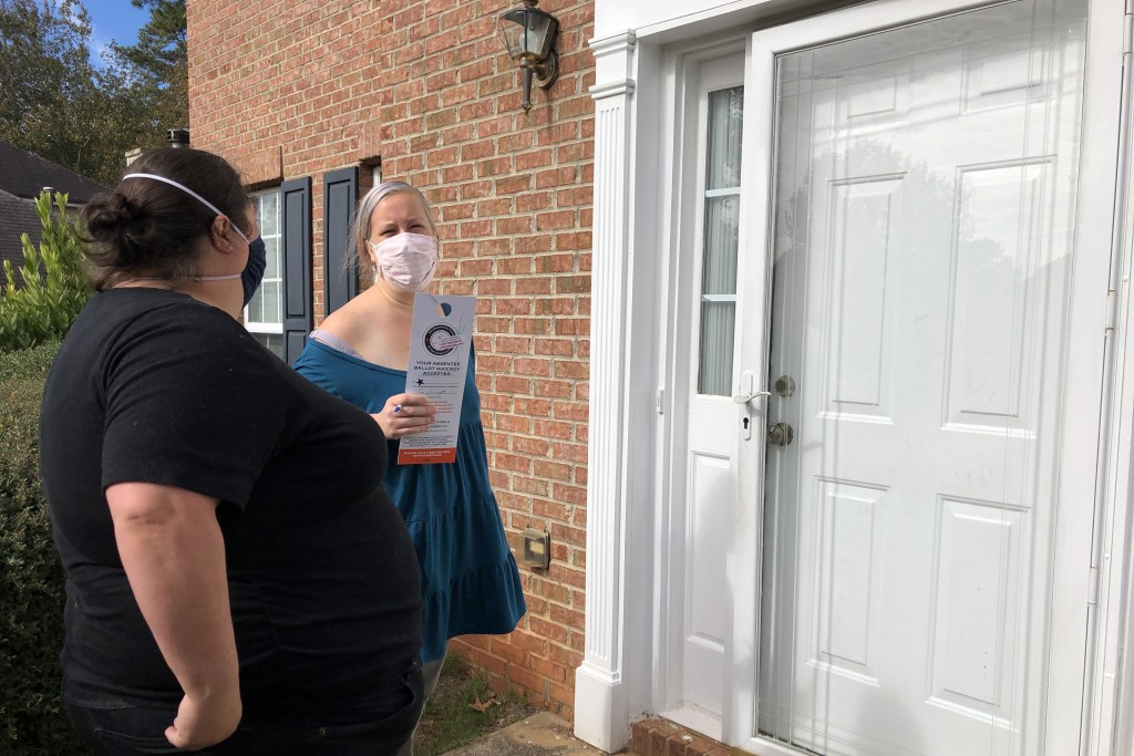 Sarah Meng, left, and Christin Clatterbuck wait for someone to answer the door at a home in Lilburn, Ga., Friday, Nov. 6, 2020, where they had informa...