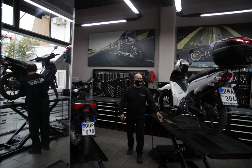 Makis Sifneos, mechanic and owner of a motorcycle repair shop works in Athens, Greece, Friday, Nov. 6, 2020. In times when a pandemic unleashes death ...