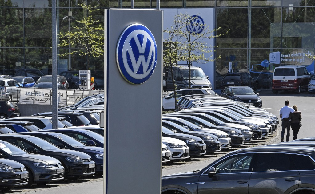 In this April 20, 2020 file photo, a Volkswagen car dealer is open in Essen, Germany. In times when a pandemic unleashes death and poverty, the concep...