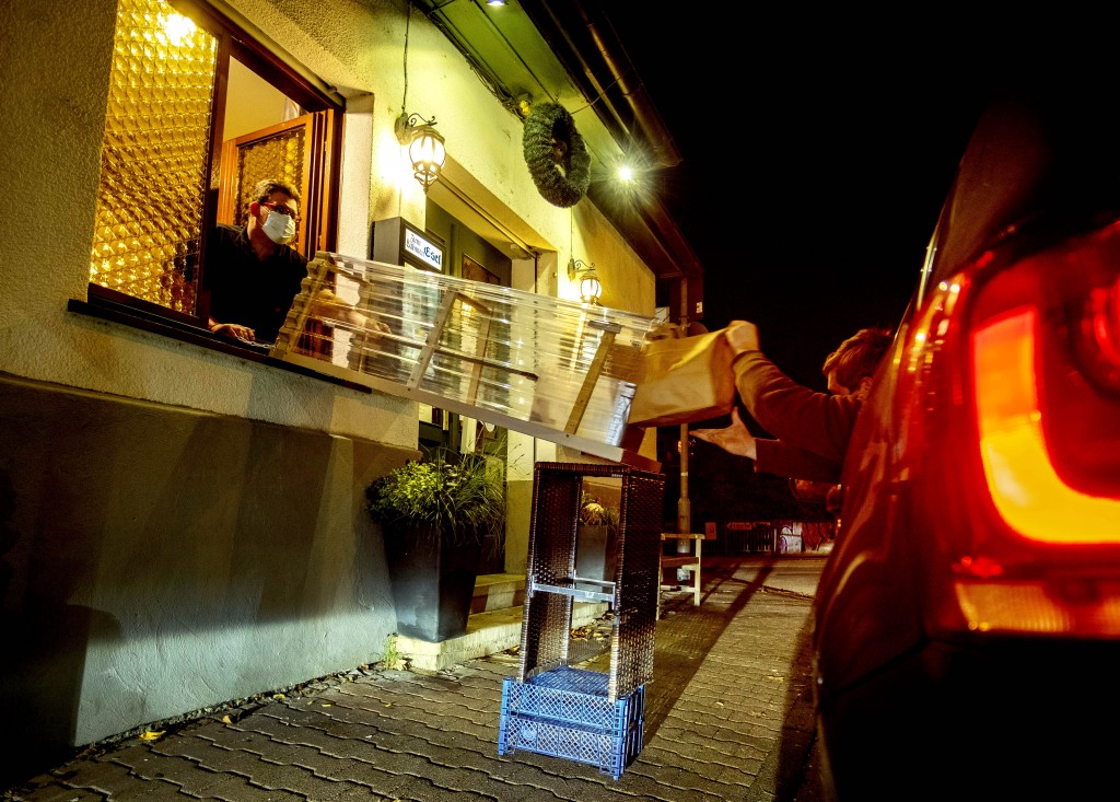 In this Thursday, Nov. 5, 2020, a box with food slides down to a car from a window of the apple cider restaurant in 'Zum Lahmen Esel' in Frankfurt, Ge...