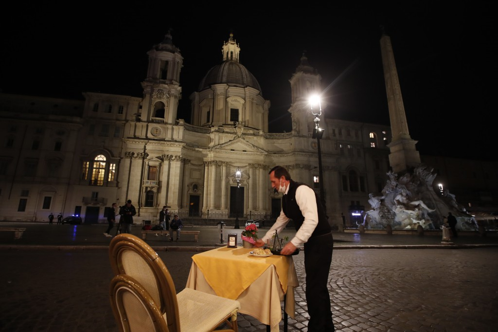 In this Oct. 23, 2020 file photo, a waiter clears a table at a cafe in Piazza Navona Square before the start of a curfew. In times when a pandemic unl...