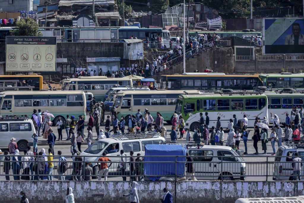 Passengers queue to get on buses in the capital Addis Ababa, Ethiopia Friday, Nov. 6, 2020. Ethiopia's prime minister says airstrikes have been carrie...