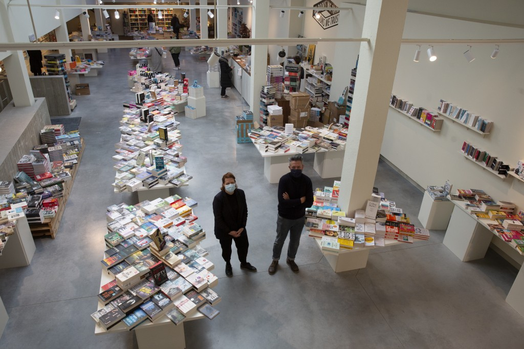 Owners of 't Stad Leest, Wouter Cajot, right, and his partner Sofie Van der Ven, pose in the middle of their bookstore in Antwerp, Belgium, Wednesday,...