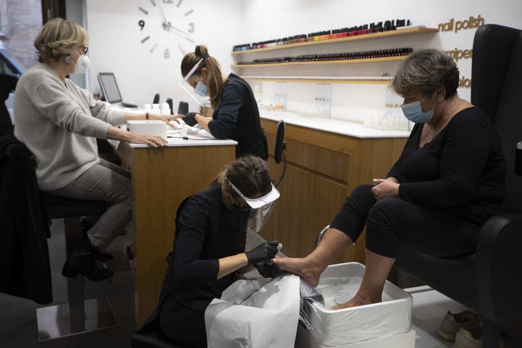 Women perform manicures and pedicures on customers in a beauty center in downtown Rome, Friday, Nov. 6, 2020. In times when a pandemic unleashes death...