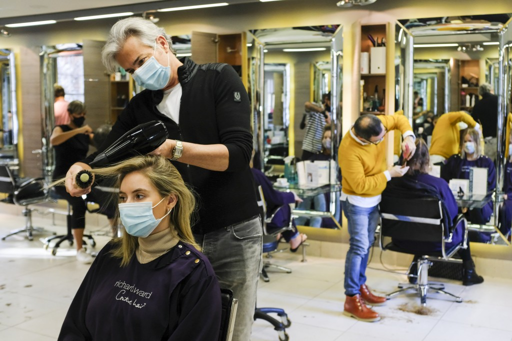 In this Wednesday, Nov. 4, 2020 file photo, Richard Ward, owner of Richard Ward Hair & MetroSpa wears a protective face mask as he works in his salon ...