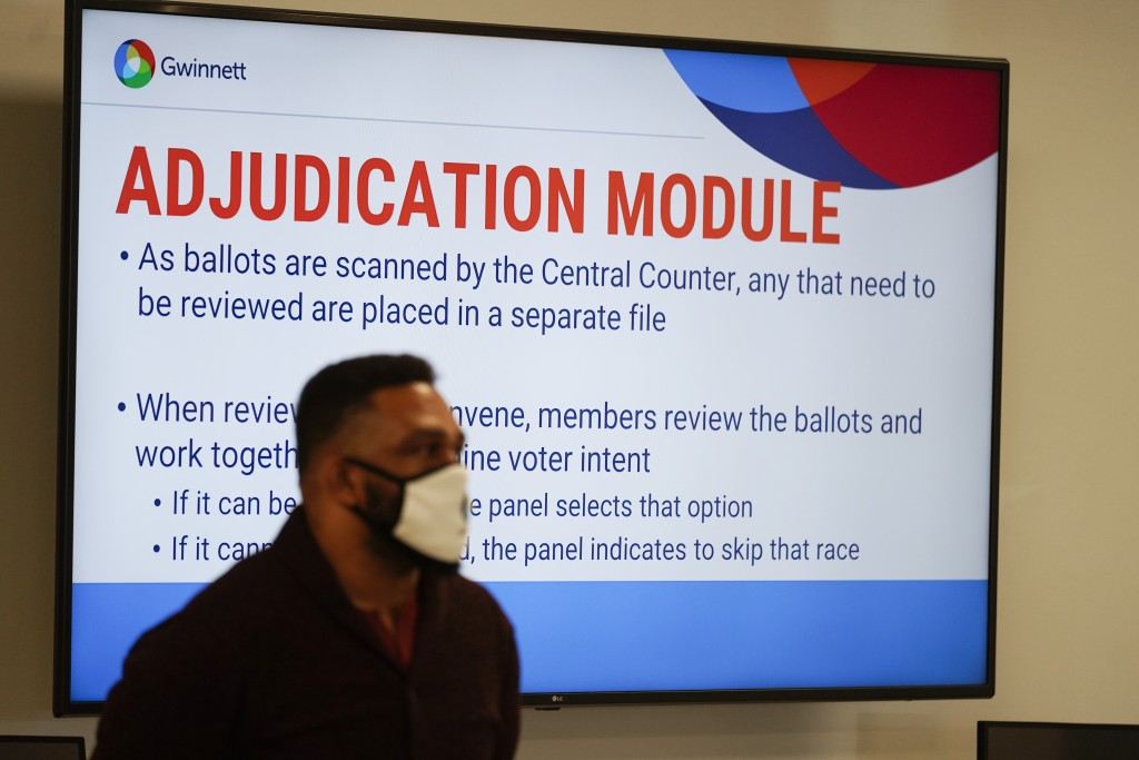A poll worker looks on as officials survey ballots at the Gwinnett County Voter Registration and Elections Headquarters, Friday, Nov. 6, 2020, in Lawr...