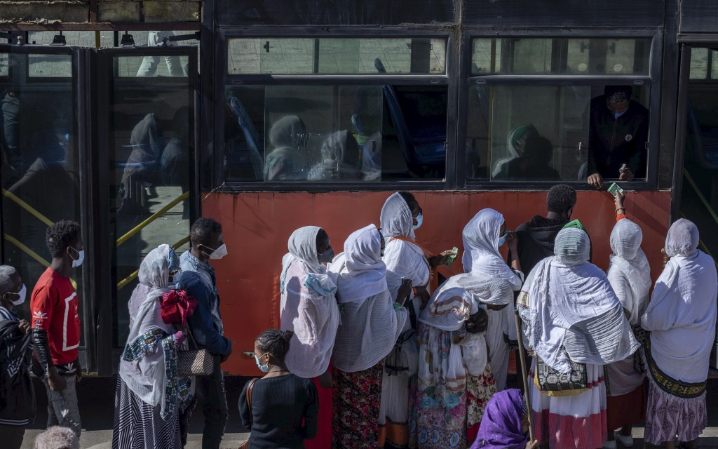 Passengers queue to get on a bus in the capital Addis Ababa, Ethiopia Friday, Nov. 6, 2020. Ethiopia's prime minister says airstrikes have been carrie...