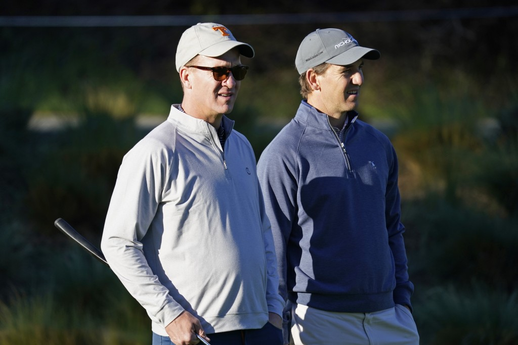 FILE - In this Feb. 6, 2020 file photo, Peyton Manning, left, and his brother Eli Manning wait to hit from the first tee of the Spyglass Hill Golf Cou...