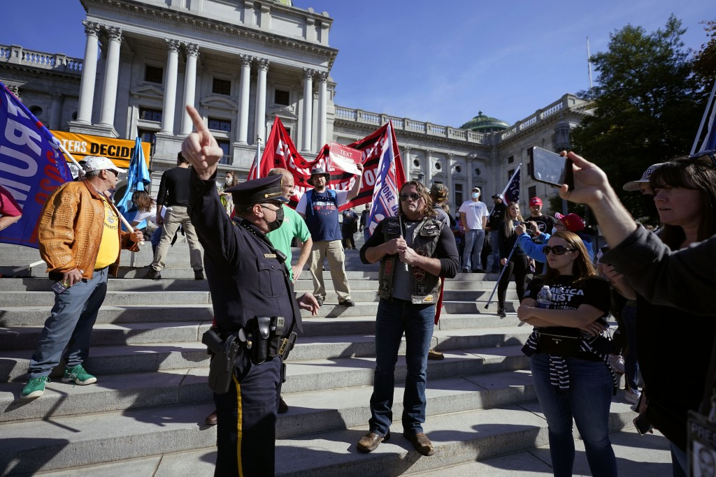 A police officer directs supporters of President Donald Trump away from the Pennsylvania State Capitol Plaza where they did not have a permit to demon...