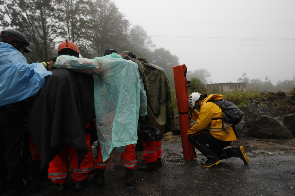 Volunteer firefighters huddle in prayer before beginning a search and rescue operation in San Cristobal Verapaz, Saturday, Nov. 7, 2020, in the afterm...