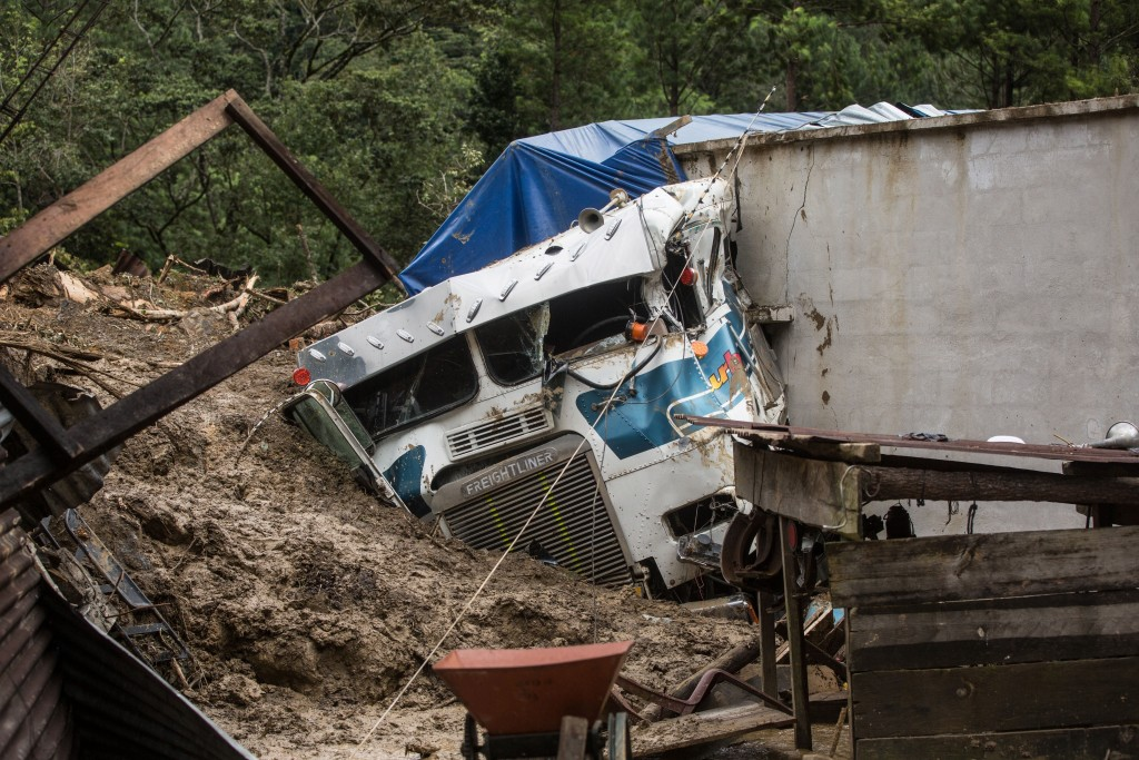A semi is partially buried in a massive, rain-fueled landslide in the village of Queja, in Guatemala, Saturday, Nov. 7, 2020, in the aftermath of Trop...
