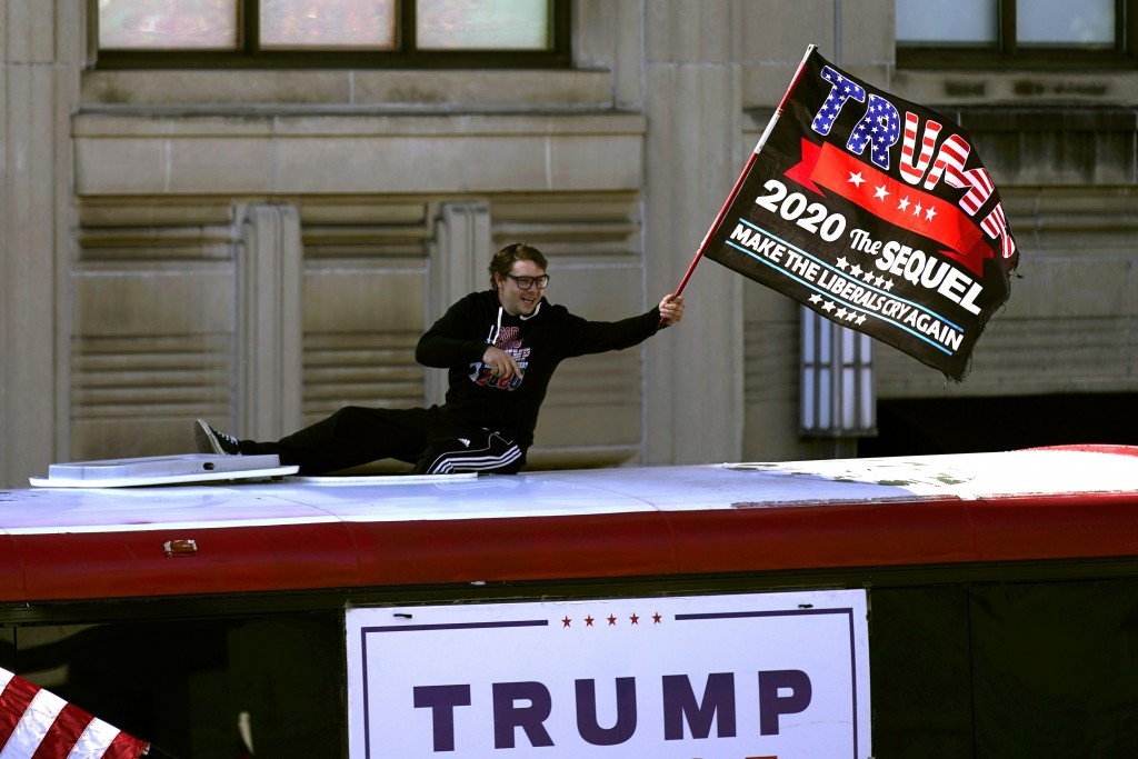 A supporter of President Donald Trump waves a flag from atop a bus outside the Pennsylvania State Capitol, Saturday, Nov. 7, 2020, in Harrisburg, Pa.,...