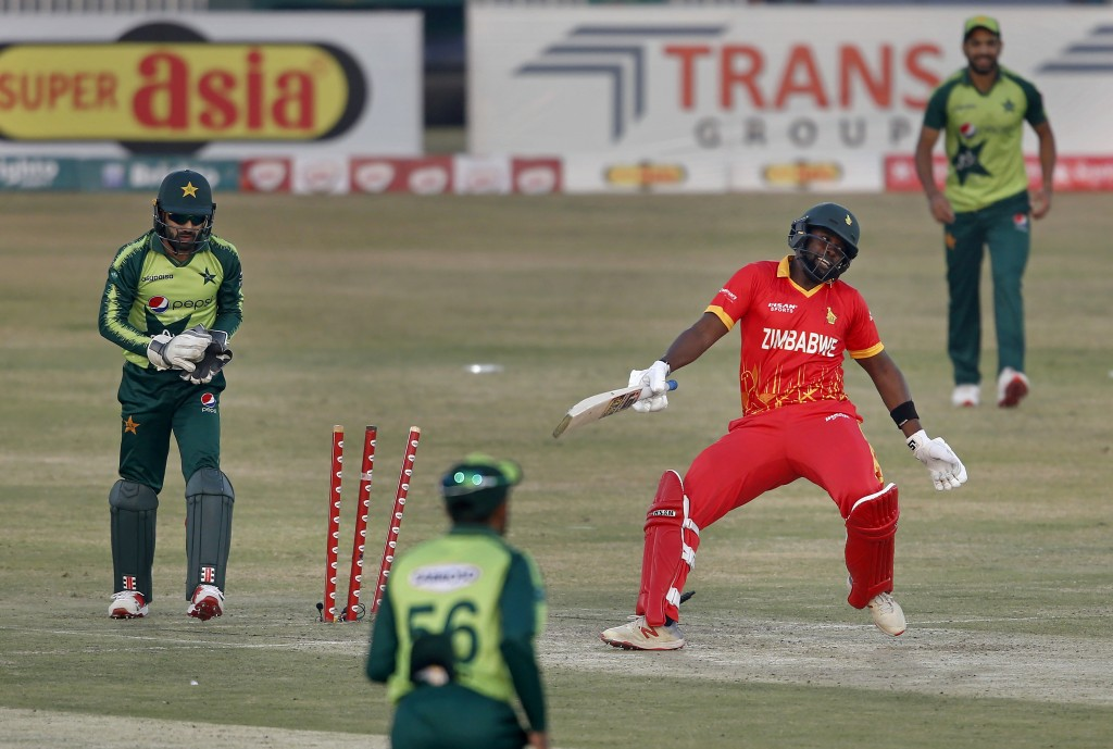 Pakistani wicketkeeper Mohammad Rizwan, left, reacts after stump out to Zimbabwe's batsman Elton Chigumbura, in red, during their 2nd Twenty20 cricket...