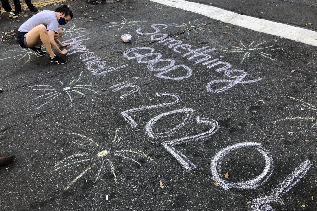 FILE - In this Nov. 7, 2020, file photo, Jolin Polasek draws a sign in chalk on a street in Harlem, New York to celebrate President-elect Joe Biden's ...
