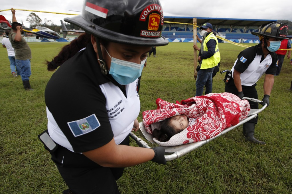 A girl rescued from the zone where residents are believed buried by a massive, rain-fueled landslide, is carried on a stretcher to a waiting ambulance...