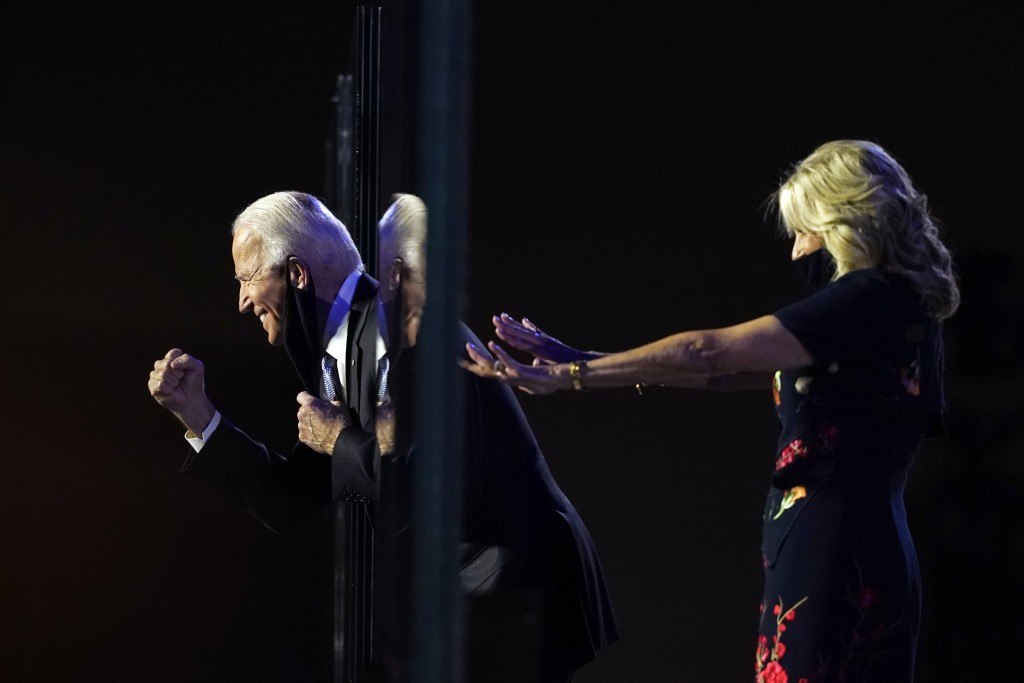 President-elect Joe Biden stands on stage with his wife Jill Biden as he leans past the protective glass, Saturday, Nov. 7, 2020, in Wilmington, Del. ...