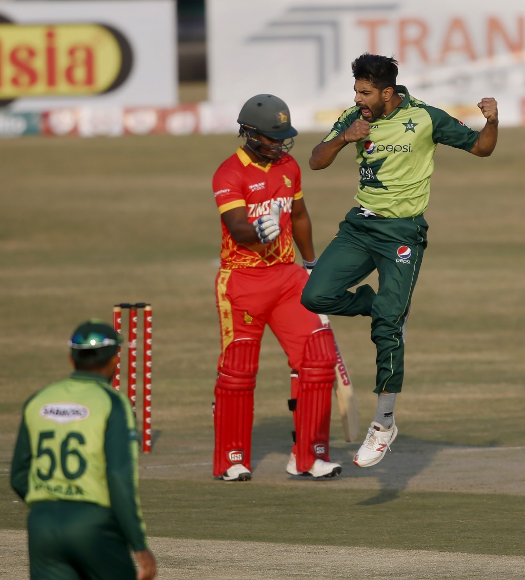 Pakistani pacer Haris Rauf, right, jumps to celebrate after taking the wicket of Zimbabwe's batsman Chamu Chibhabha, in red, during their 2nd Twenty20...