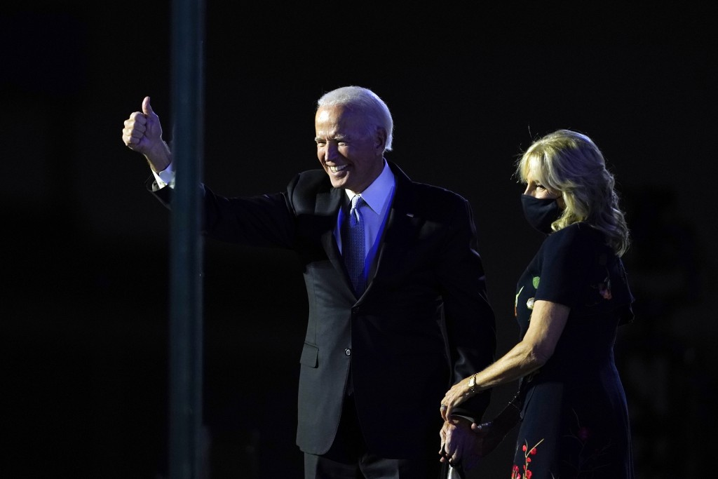 President-elect Joe Biden stands on stage with his wife Jill Biden as he gives the thumbs-up to the cheering crowd beyond the protective glass, Saturd...