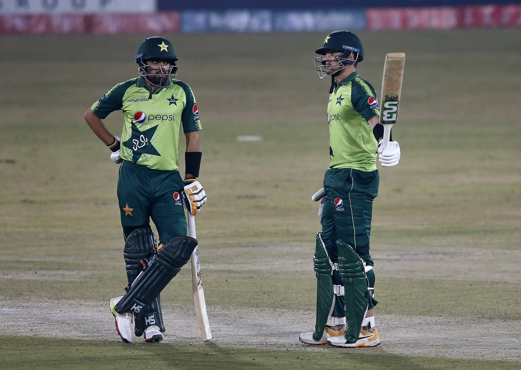 Pakistani batsman Haider Ali, right, raises bat to celebrate his fifty while teammate Babar Azam watches during the 2nd Twenty20 cricket match against...
