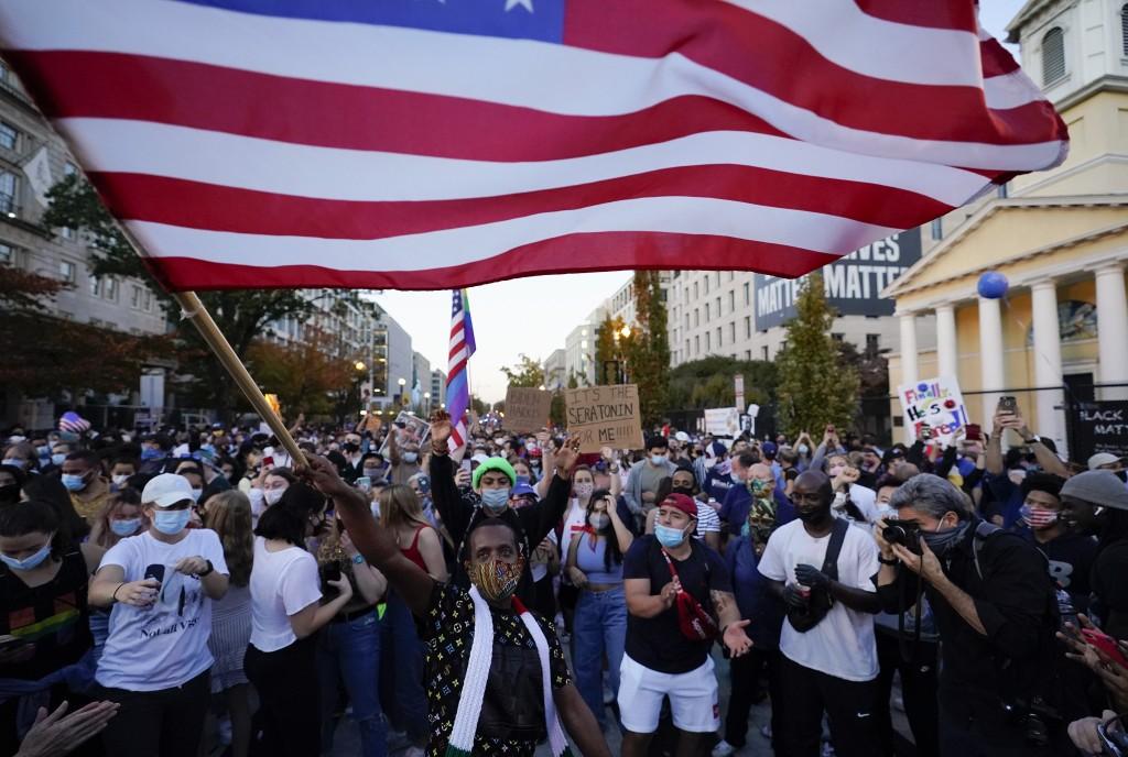 FILE - In this Nov. 7, 2020, file photo, people gather in Black Lives Matter Plaza to celebrate President-elect Joe Biden's win over President Donald ...