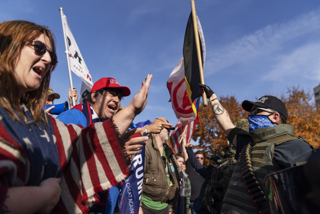 Trump supporters, at left, demonstrating the election results are confronted by counter protesters at the State Capitol in Lansing, Mich., Saturday, N...