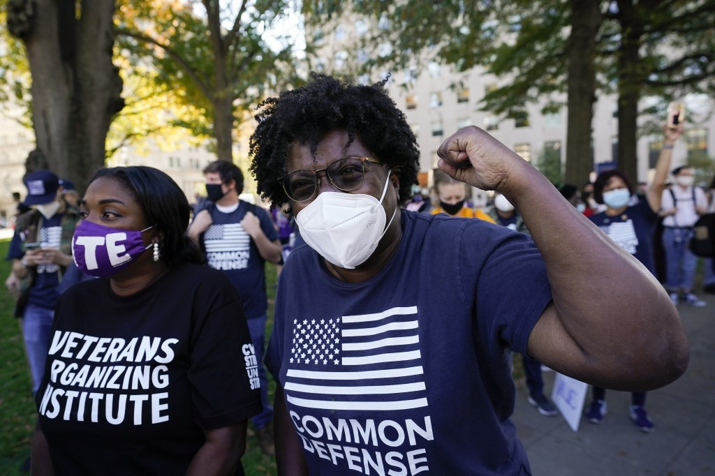 People gathered in Black Lives Matter Plaza, react to the presidential race being called in Joe Biden's favor, Saturday, Nov. 7, 2020, in Washington. ...