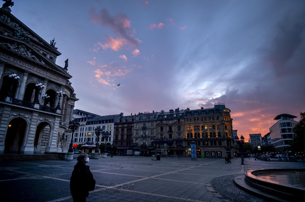 A woman wearing a face mask walks past the Old Opera, left, in Frankfurt, Germany, before sunrise on Monday, Nov. 9, 2020. (AP Photo/Michael Probst)