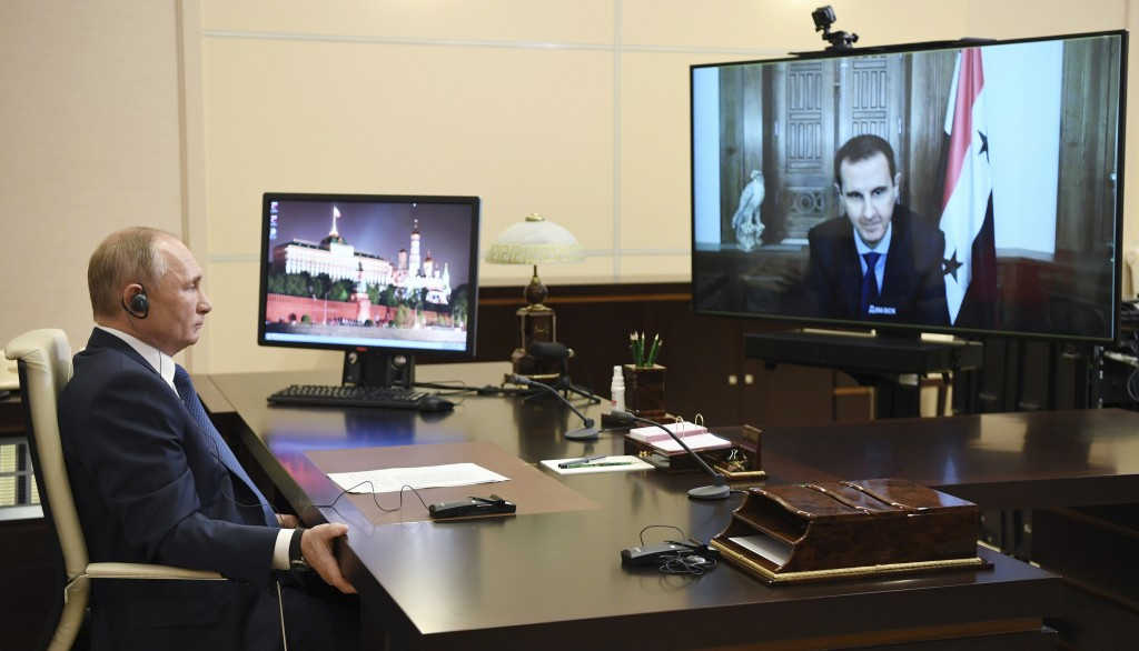 Russian President Vladimir Putin, listens to Syrian President Bashar Assad, right on screen, during their talks via video conference at the Novo-Ogary...