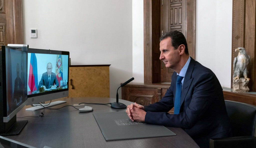 In this photo released by the Syrian official news agency SANA, Syrian President Bashar Assad listens to Russian President Vladimir Putin during their...
