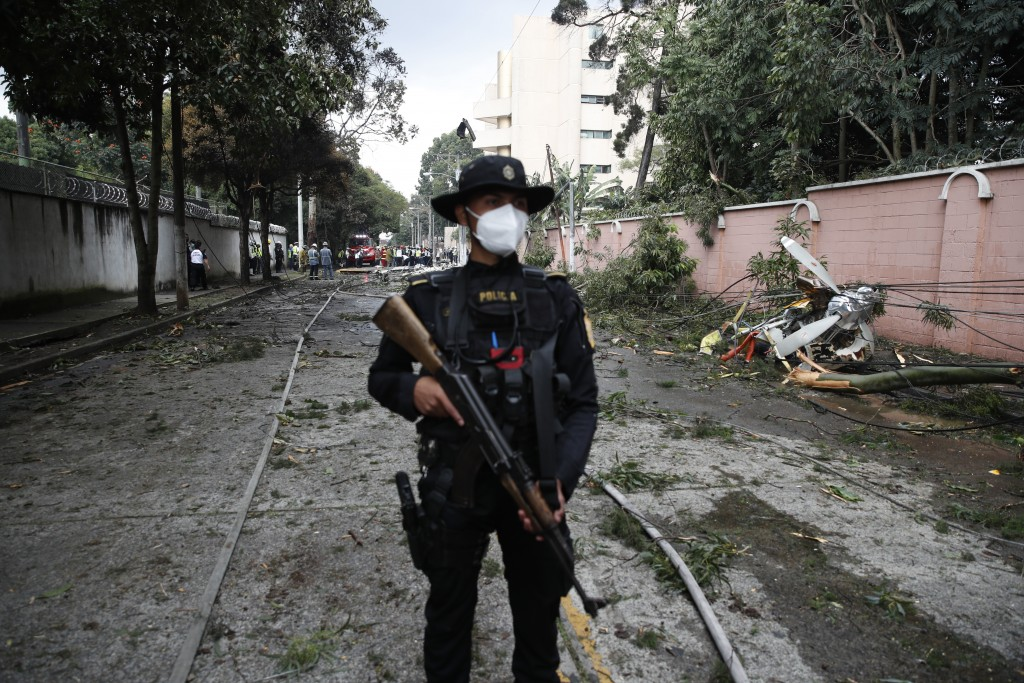 A policeman stands guard at the area where a plane that crashed in Guatemala City, Sunday, Nov. 8, 2020. A plane crashed after taking off from Guatema...