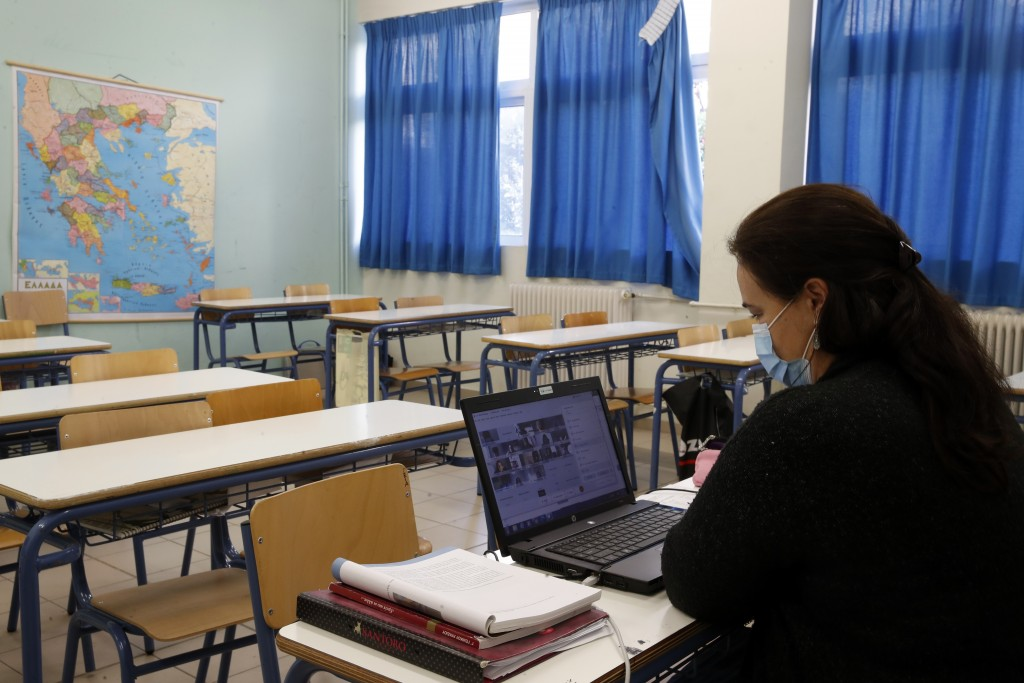 Literature teacher Angeliki Baladima, wearing a face mask to prevent the spread of coronavirus, gives an online lesson to high school students in an e...