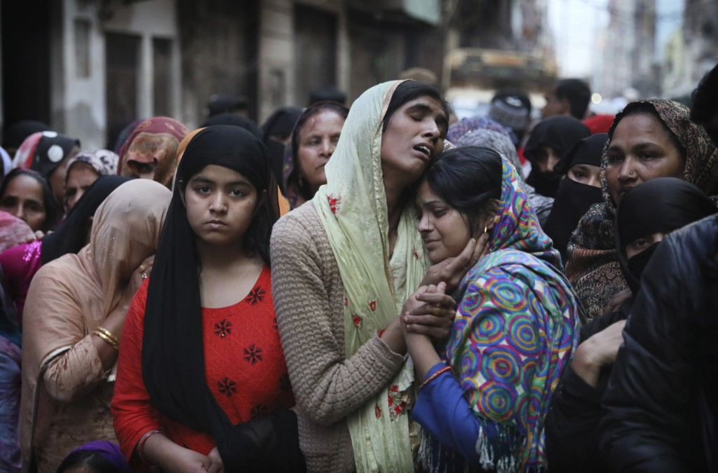 FILE- In this Feb. 27, 2020 file photo, relatives and neighbors wail near the body of Mohammad Mudasir, 31, who was killed in communal violence in New...