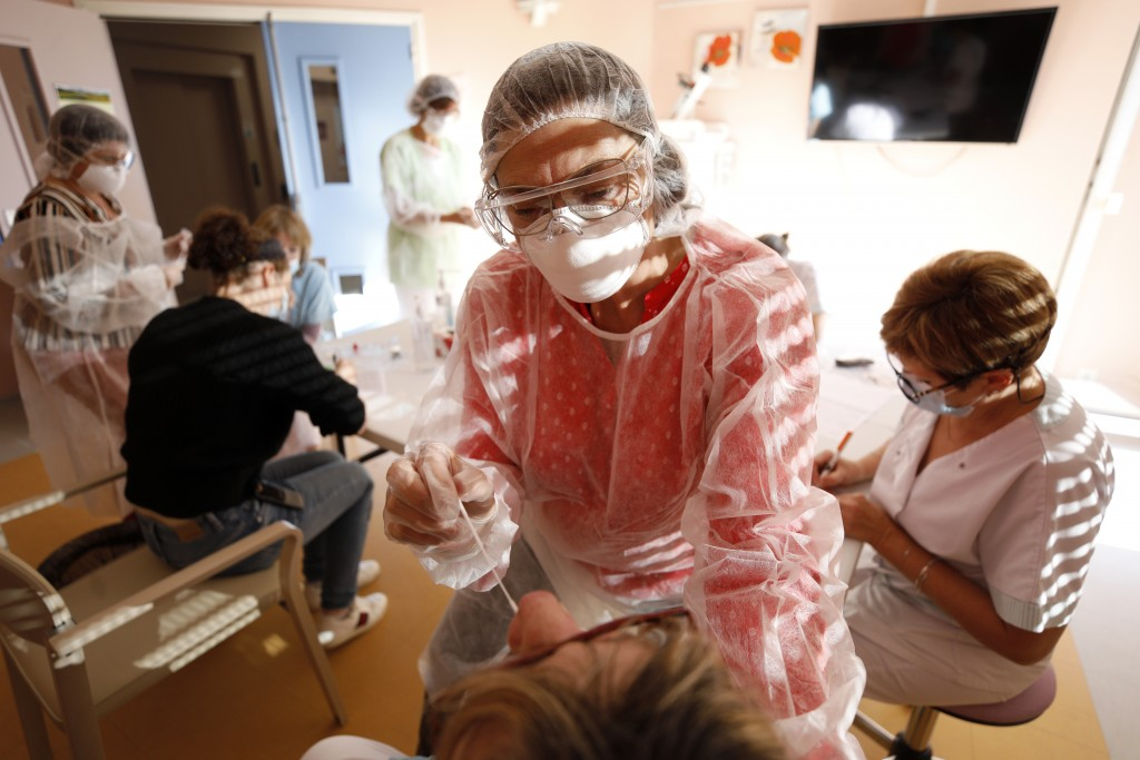 Workers of a nursing home are being tested with a PCR test in Ammerschwihr, eastern France, Monday, Nov.9, 2020. The antigen tests can give results in...