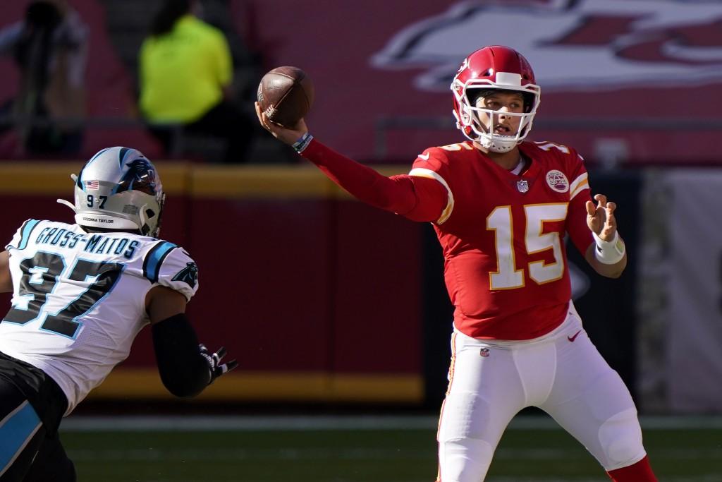 Kansas City Chiefs quarterback Patrick Mahomes (15) passes as Carolina Panthers defensive end Yetur Gross-Matos (97) applies pressure during the secon...