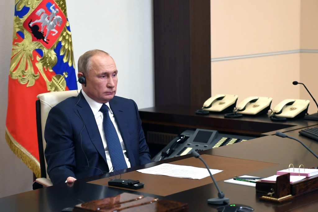 Russian President Vladimir Putin, listens to Syrian President Bashar Assad, on a screen, during their talks via video conference at the Novo-Ogaryovo ...