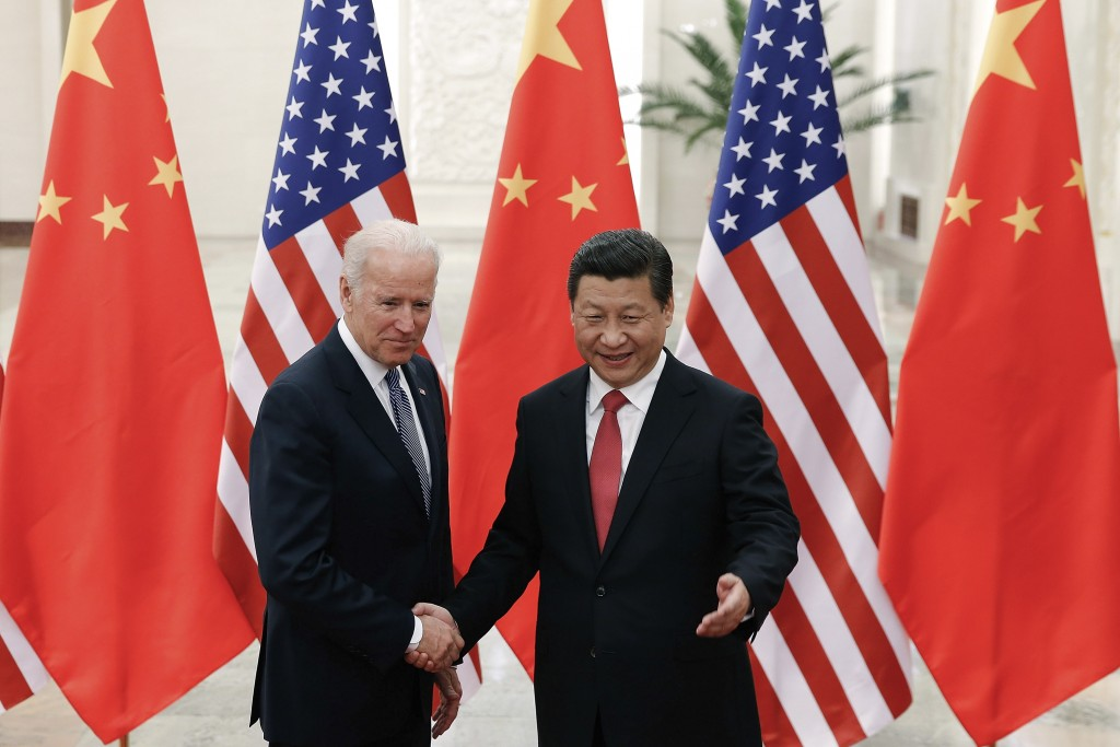 FILE - In this Dec. 4, 2013, file photo, Chinese President Xi Jinping, right, shakes hands with then U.S. Vice President Joe Biden as they pose for ph...