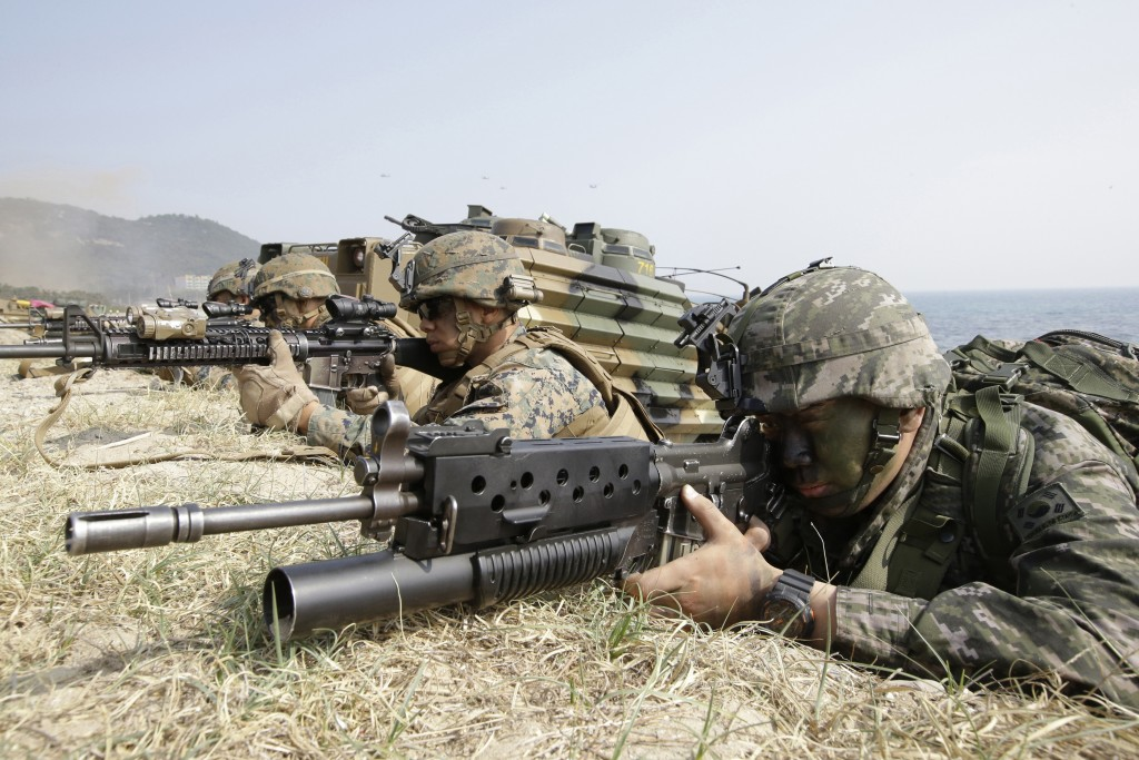 FILE - In this March 30, 2015, file photo, marines of South Korea, right, and the U.S aim their weapons near amphibious assault vehicles during U.S.-S...