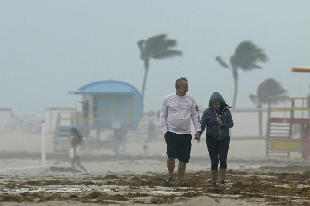 A couple walks along the beach during a downpour, Sunday, Nov. 8, 2020, on Miami Beach, Florida's famed South Beach. A strengthening Tropical Storm Et...