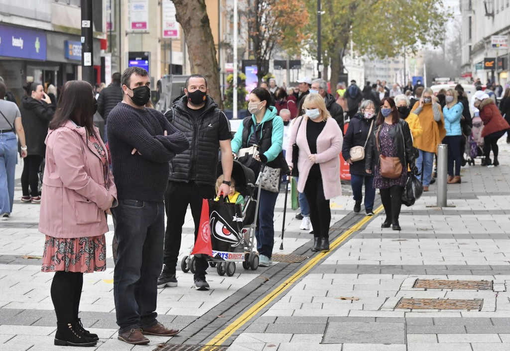 Shoppers queue to enter shops in Cardiff, Wales, Monday Nov. 9, 2020, after restrictions imposed by the Welsh government are relaxed following a two-w...