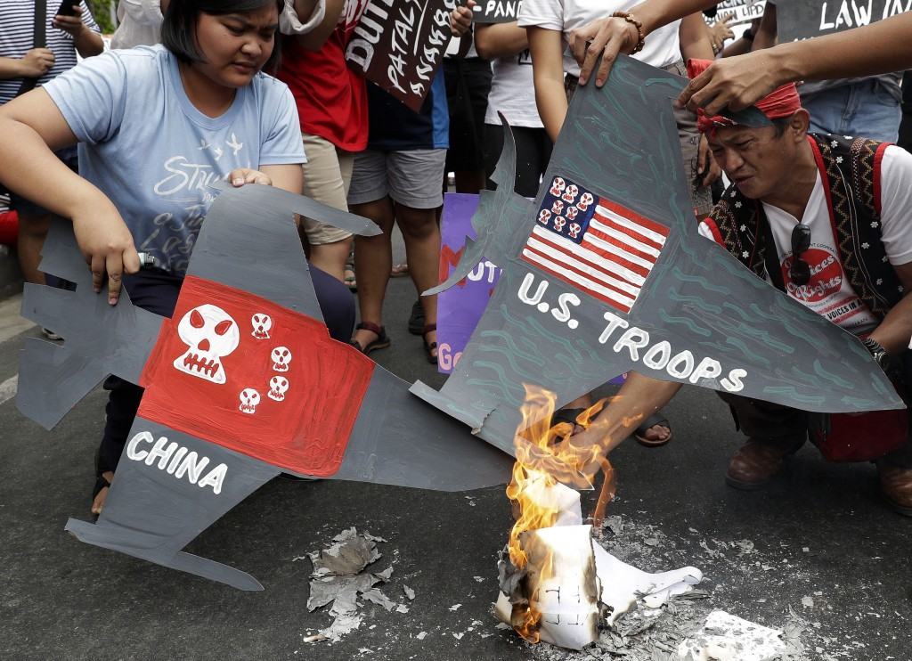 FILE - In this March 5, 2019, file photo, protesters burn cardboard-cut jet fighters with mock U.S. and China flags as they hold a protest in front of...