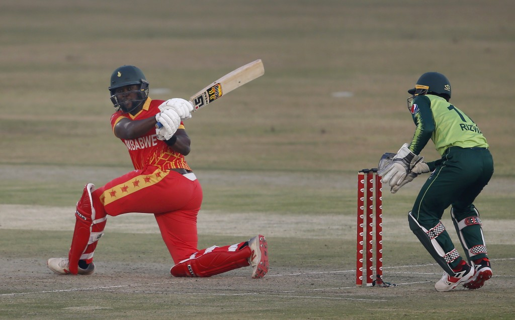 Zimbabwe's batsman Elton Chigumbura, left, follows the ball after playing a shot during their 3rd Twenty20 cricket match against Pakistan at the Pindi...