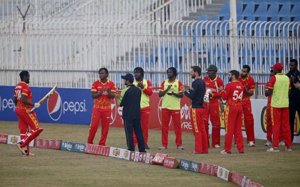 Zimbabwe's players clap for their teammate Elton Chigumbura, left, who is playing his last match, as he walks back to pavilion after his dismissal dur...