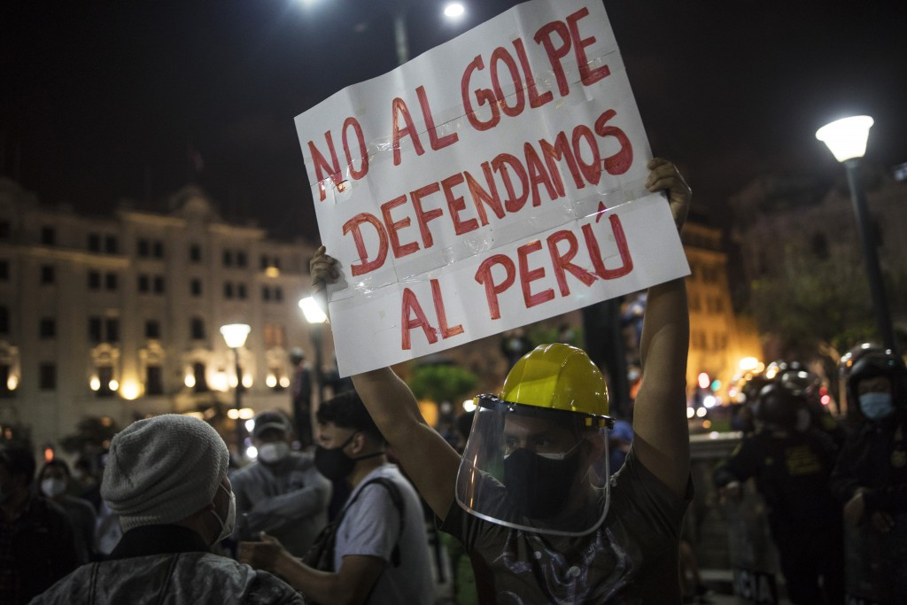 """A pro-government protester holds a banner that reads in Spanish: """"Not to the coup let's defend Peru,"""" while gathering in Plaza San Martin square in Li..."""