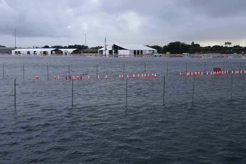 A parking lot at Hard Rock Stadium, the site of one of the major COVID-19 testing sites in the state, is flooded in the aftermath of Tropical Storm Et...
