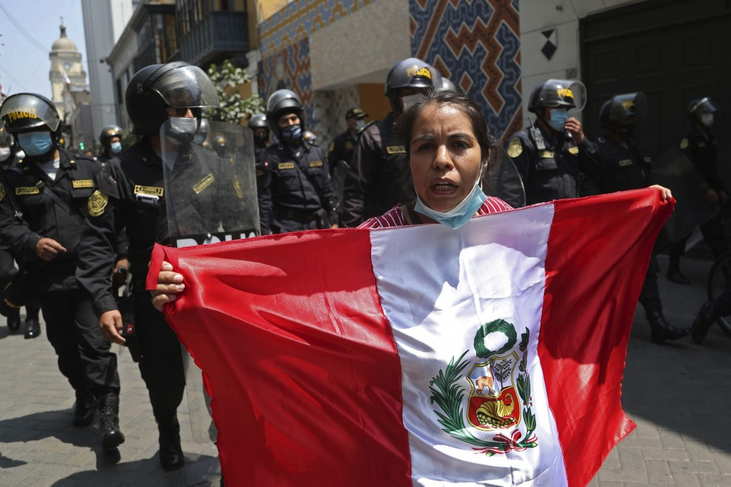 An anti-government protester holds the Peruvian flag and chants against Peru's President Martin Vizcarra who faces an impeachment vote, near Congress,...