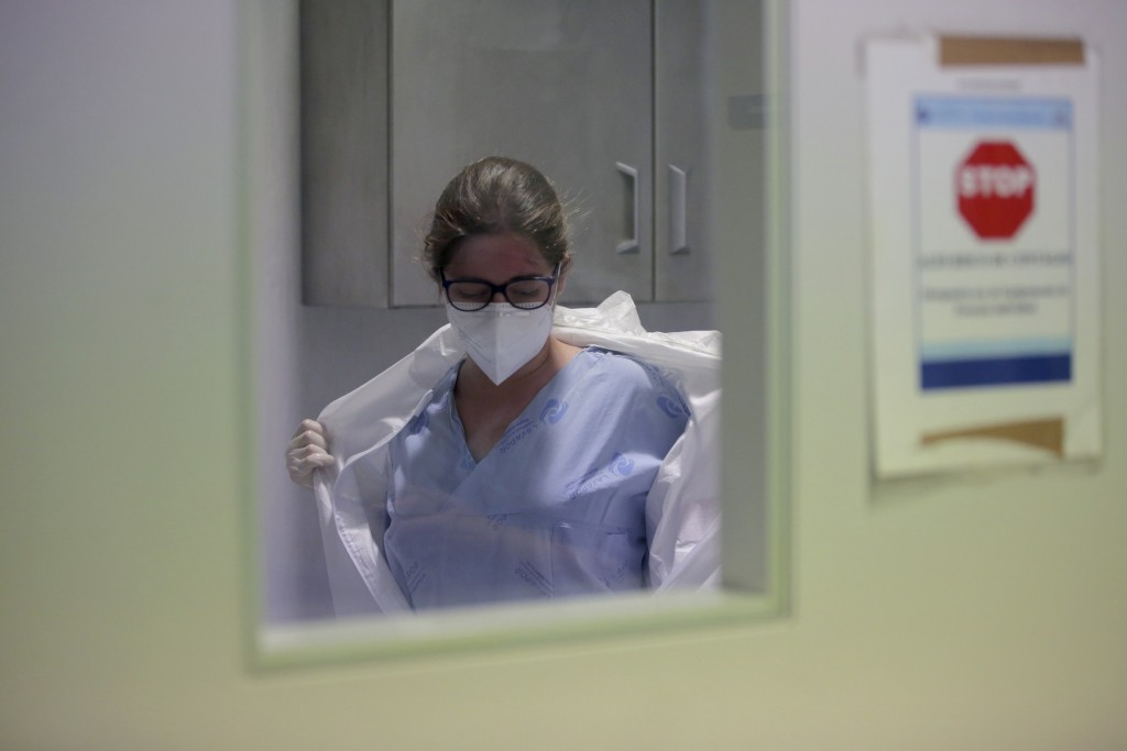Nurse Viviana takes off her protective suit after finishing a round tending to COVID-19 patients inside negative pressure rooms at the Curry Cabral ho...