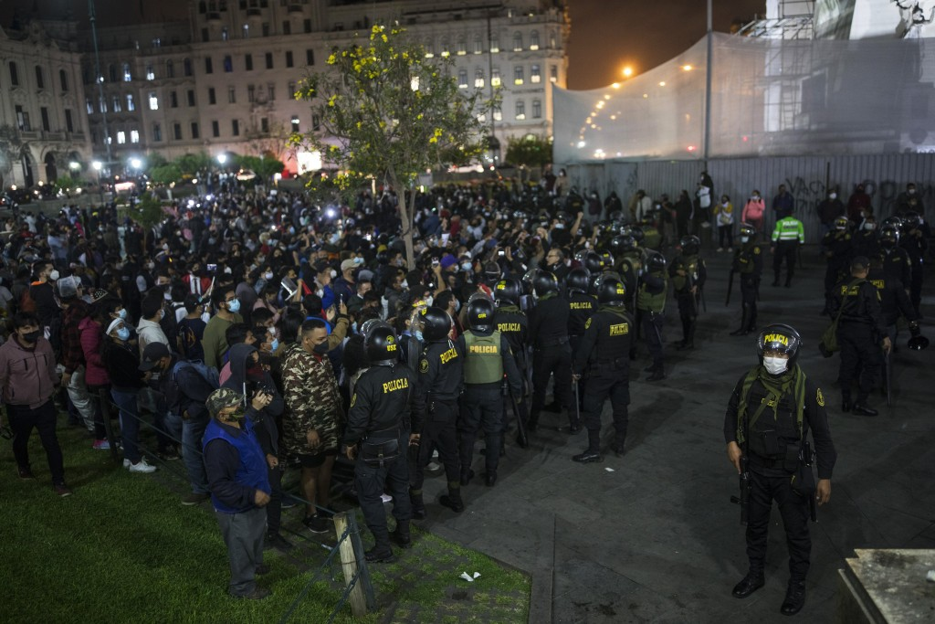 Riot police stand guard as pro-government protesters gather in Plaza San Martin square in Lima, Peru, Monday, Nov. 9, 2020. (AP Photo/Rodrigo Abd)