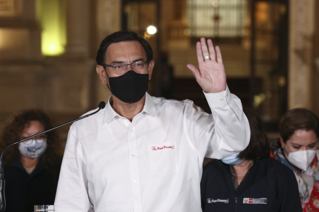 Peru's President Martin Vizcarra waves to reporters during a press conference at the presidential palace in Lima, Peru, after lawmakers voted his impe...