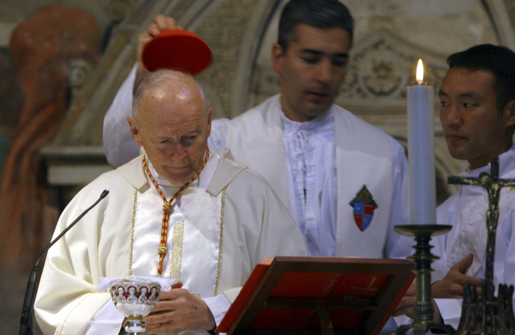 FILE - In this April 14, 2005 file photo, an aide covers the head of Washington, D.C. Cardinal Theodore McCarrick during a Mass in St. Nereus and Achi...
