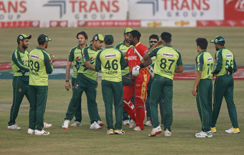 Pakistan's players greet Zimbabwe's batsman Elton Chigumbura, who will play his last match during their 3rd Twenty20 cricket match at the Pindi Cricke...